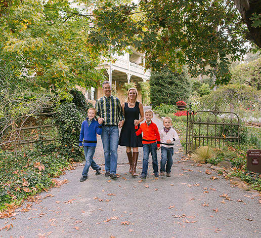 Hugh and Monique Davies and their three sons strolling through wrought iron gate of the historic Victorian house